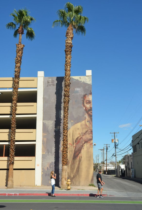 a large mural on the corner of a 4 storey parking garage, a man from the waist up who is looking down on the sidewalk - viewed from straight on so only one half of the mural, and one half of the man, is visible