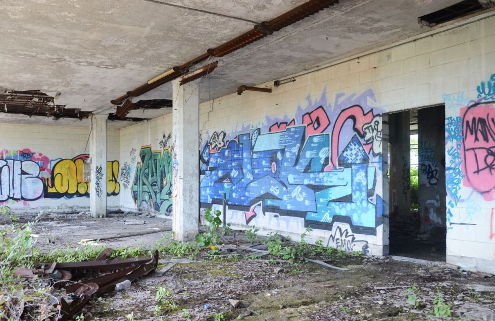 graffiti on the walls of an abandoned building, blue and green tags