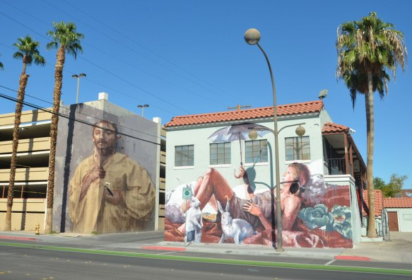 Two large murals on two different buildings that are across the alley from each other. On the left is a large man by Borondo and on the right is a woman reclining on a beach by Finton Magee. She is holding a purple umbrella. There are also cabbages and white rabbits in the scene.