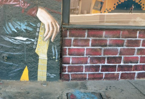 signature at the bottom of a portrait of a guitar player, a hand holding a fender guitar is in the picture along with part of the brick wall of the building.