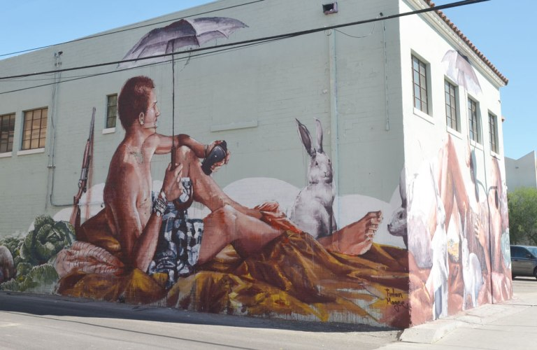 looking at a corner of a two storey white building with a mural painted on the two sides. On the side closest to the camera ia man sitting and holding an umbrella. He is wearing shorts and is topless. A rifle is behind him, white rabbits are also in the picture.