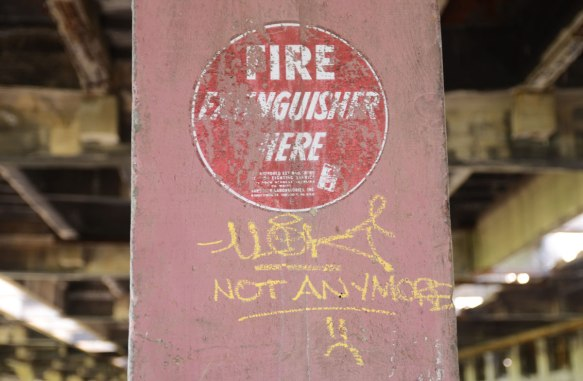 pink concrete post with an old painting on it, red circle with white words that says fire extinguisher here. Someone has written in yellow below it, not anymore.