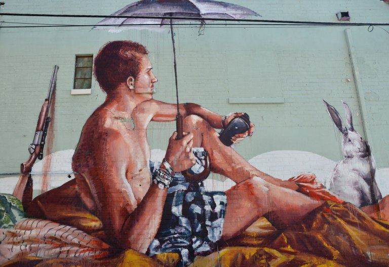 mural of a man holding an umbrella as he sits on the ground. A rifle is behind him. He is holding a small black case in one hand.
