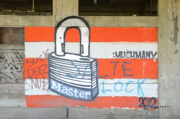red and white horizontal striped square painted on a wall of an abandoned building with a drawing of a padlock on top of it. Brand name of the lock is master.