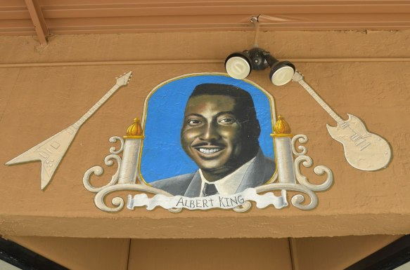portrait of Albert King (head shot) on the outside of a guitar store