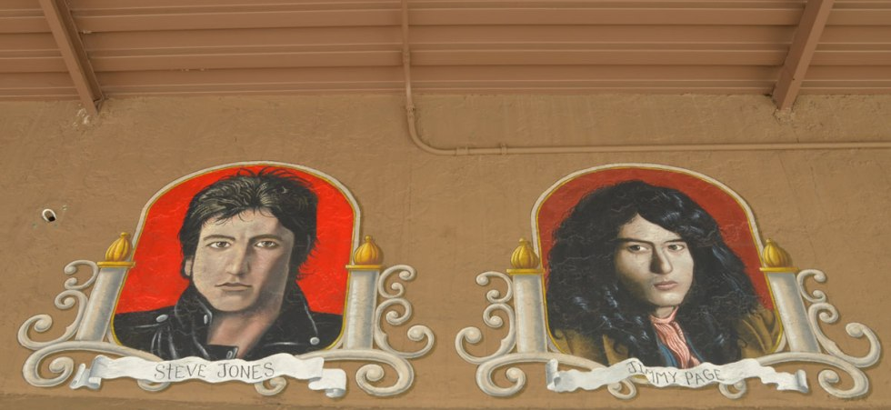 portraits of two guitar players (head shots) on the outside of a guitar store