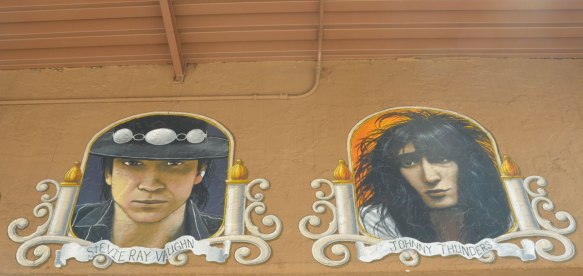 portraits of two guitar players (head shots) on the outside of a guitar store - Stevie Ray Vaughan and Johnny Thunders