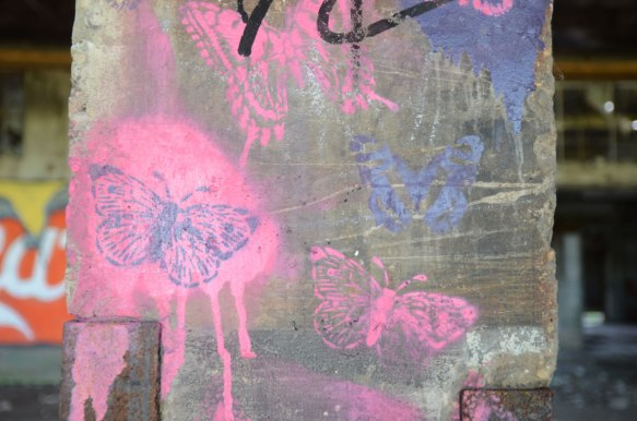 pink and purple stencilled butterflies on a concrete post