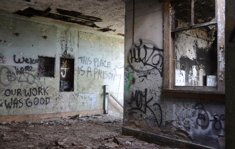 Words and other graffiti written on grey walls of an abandoned train station in Buffalo, one set of words says This place is a prison. Another set of words says Our work was good