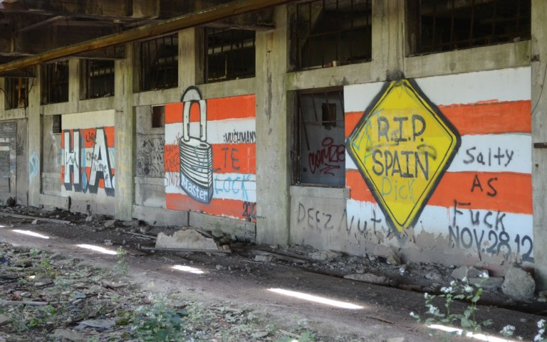 street art paintings on the walls of an abandoned train platform.