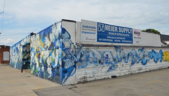 The corner of a one storey building that is covered in a blue and white bubbly looking mural. With a sign for Meier Supply, HVAC Specialists.