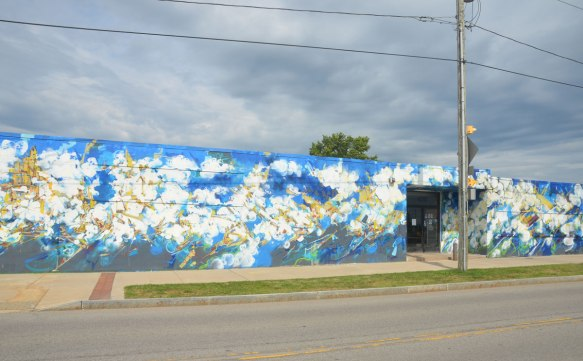 Front of a building covered with a mural in blues, yellows and white, clouds like blobs, yellow lines, very abstract mural.