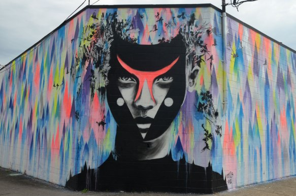 A very large man's face painted by Vexta in a mural, with a background of different coloured splotches.