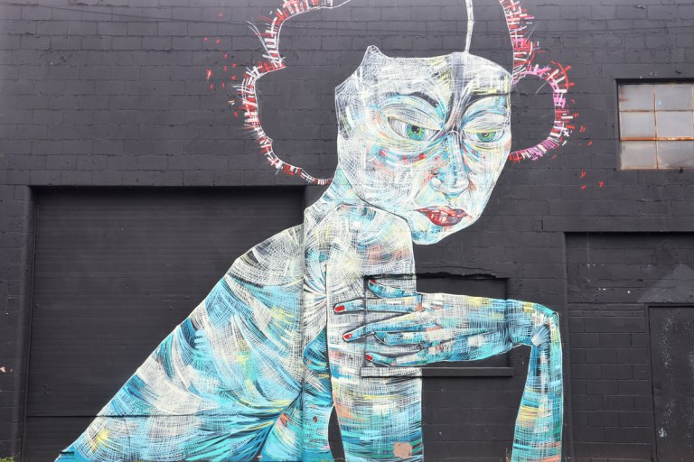 mural on the side of a black brick building, of a woman done in wide strokes of different blues, yellows and white. Upper body, mostly in profile, with her elbow bent and her hand turned towards her arm.
