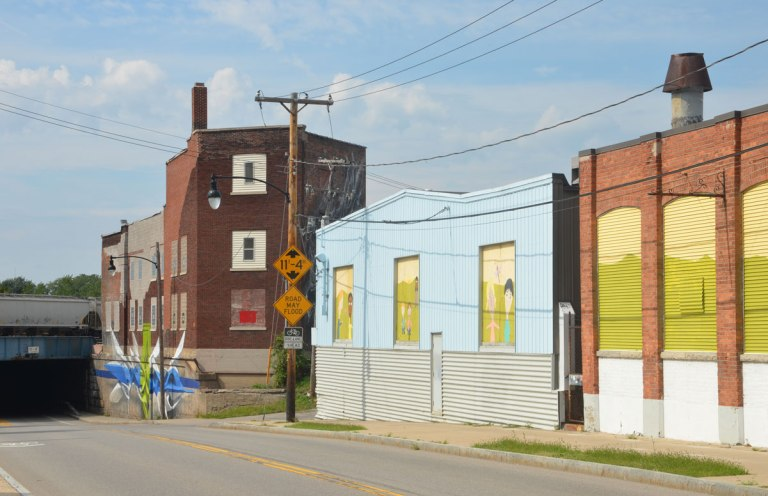 Three older buildings on Atlantic Avenue in Rochester. Two of the buildings have painted boards in their windows. The third building is a taller brick building with a mural at street level alongside the sidewalk.