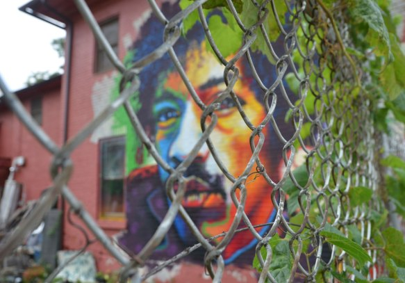 A brightly coloured man's face, that looks like the famous guitar player Jimi Hendrix, is painted on the back of a building, but it is behind a chain link fence. There is a vine growing on the fence that looks like it might be the man's hair.