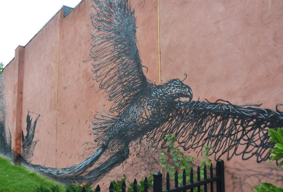 A bird in flight, street art mural, black on red brick.