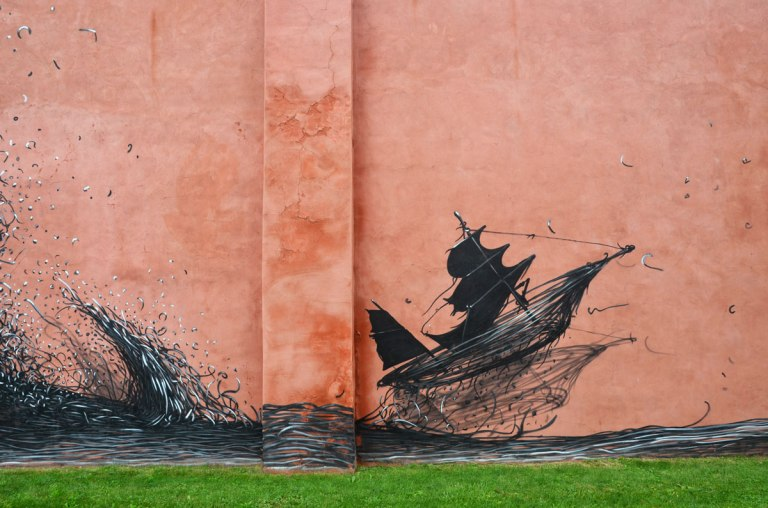 part of a mural, an abstract looking boat with a wave of water, all done in black