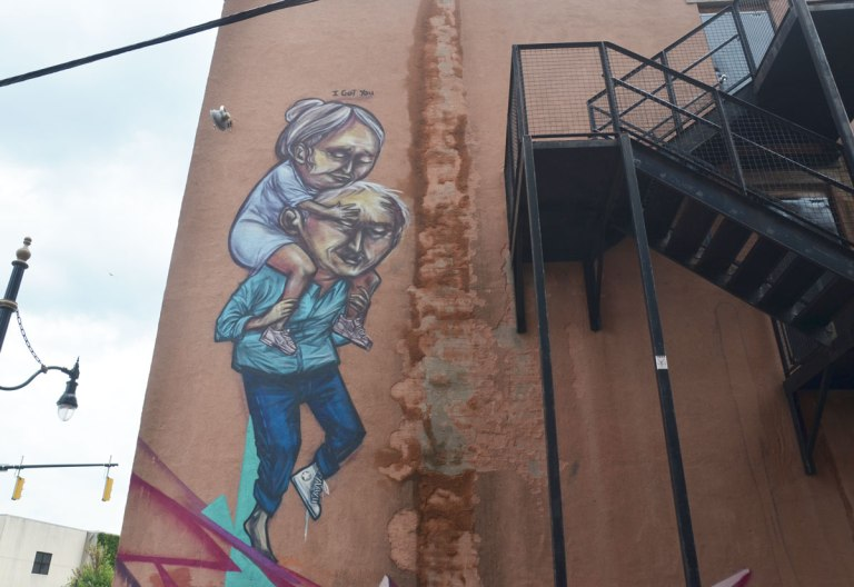 mural on the back of a red brick building, beside a metal exterior staircase, of a man carrying a woman on his back. Above the picture are the words I Got You