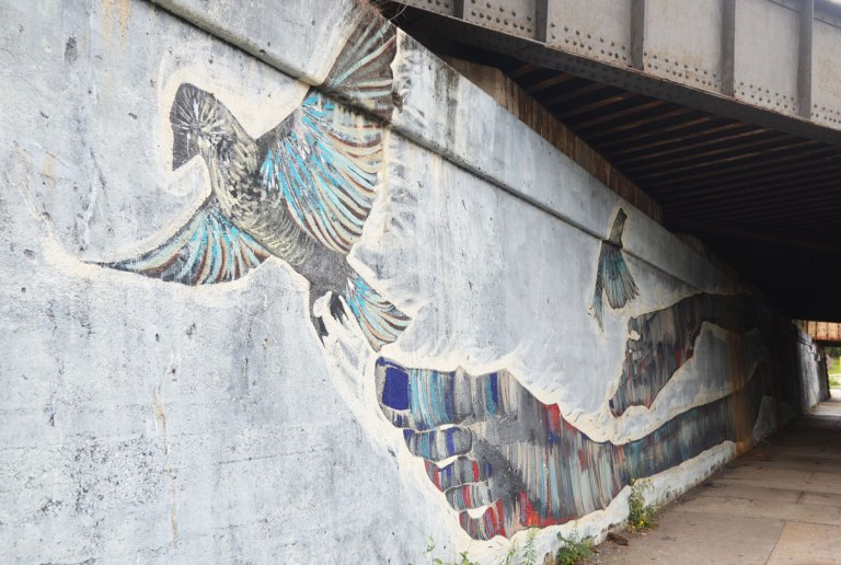 part of a long mural under a railway bridge, the end of the mural with a person's feet and large toes, with two birds also in the picture.