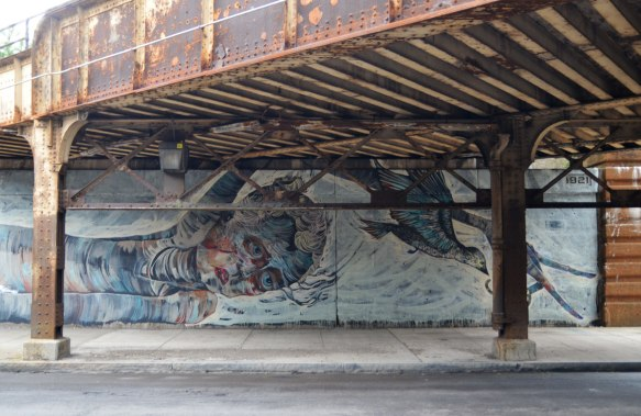 mural of a woman's head, lying on her side, under a rusty railroad bridge, by Faring Purth