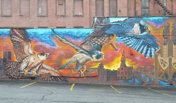 part of a mural, falcons flying over a city skyline at sunset