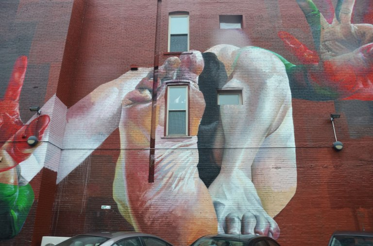 Detail of a larger mural. Showing two feet - one where the bottom of the foot is seen, and the other where the calf and toes are seen.