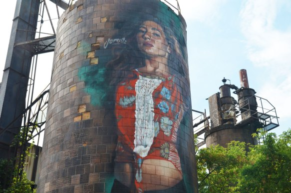 A mural by Jarus of a woman on a water tower (or silo shaped storage tower).