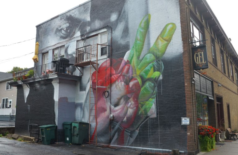 Mural of Martin Luther King on the back of a building. The building has a balcony on which is a barbecue and some chairs. In the mural, his hands are coloured, one in greens and one in reds.
