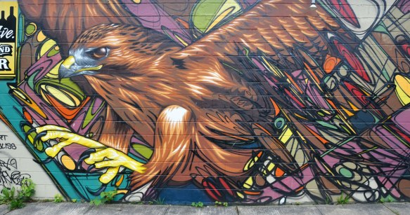 on the side of a building, large eagle taking flight