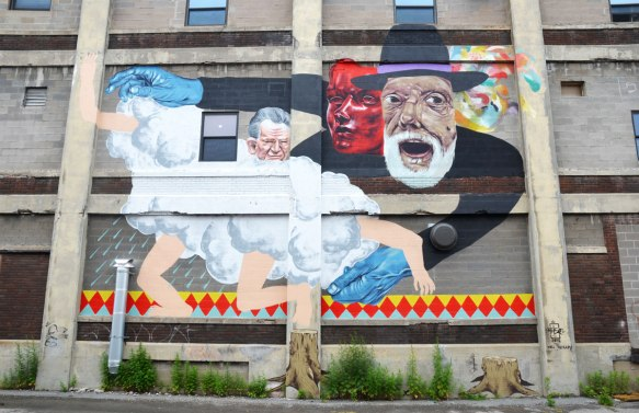 very large mural on the side of a building, three men and a cloud. One man has blue hands.