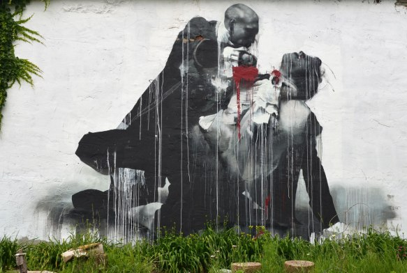 Wall Therapy mural in Rochester, on the side of a building, in black and white, what looks like one man murdering another, the blood is red which is the only colour in the painting