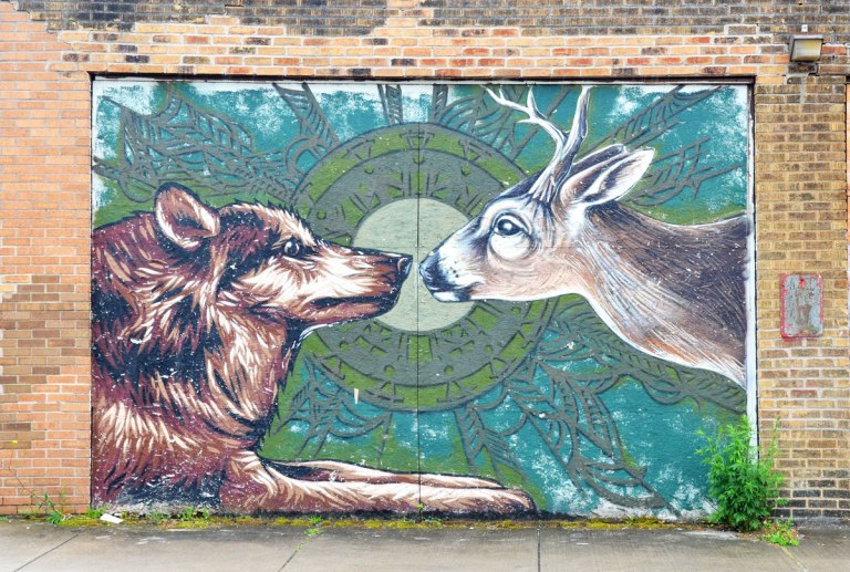 mural on a garage door of a dog and deer meeting nose to nose