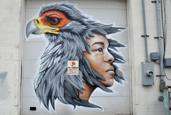mural of a boy and a bird. The bird is sitting on the boys head such that the feathers of the bird look like the boys hair.