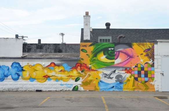 A mural on the side of a building in Rochester New York showing a large eye that is half green and half pink. Lots of swirls of colour as well. Also a small section is painted as a grid of different colours.