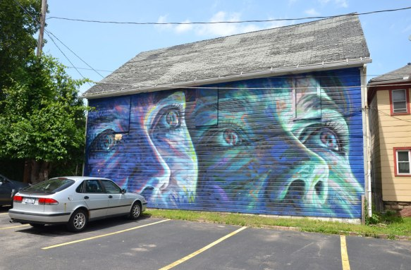 Wall Therapy mural in Rochester, on the side of a building, two large bluish faces looking up towards the sky. A car is parked in front of it.