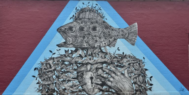 mural in a blue triangle of a person like shape with a three eyed fish as it`s head, upper body made of a tightly woven vine, heart with a keyhole in it, hand