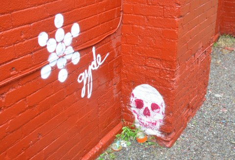 brick wall painted orange. A skull graffiti stencil is on the wall, just above ground level. A snowflake shaped graffiti in white next to it with the word gyde written in cursive