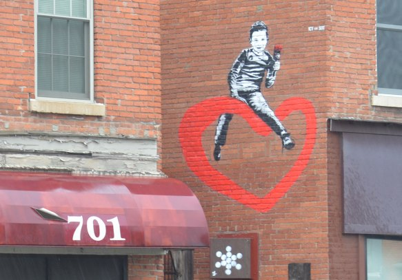 a small street art painting on the upper storey, side of a building above 701 South Ave in Rochester. A boy in black and white is straddling a large red heart. She has a red rose in her hand