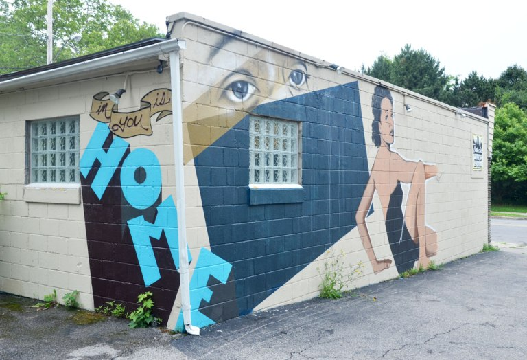 mural on the corner of a building, The word home is written in large blue letters around the corner, and on one side of the building is a pair of eyes over a real window, and a woman sitting beside the window. It looks like she is sitting on the ground, one knee up and she is turned from the waist to look back at the viewer.