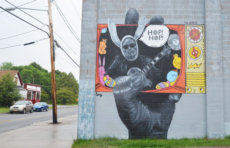 "Wall Therapy mural in Rochester, on the side of a building, a very large hand is hold a TV screen. A man with big bunny ears seems to be coming out of the screen along with a word bubble that says ""hop hop"""