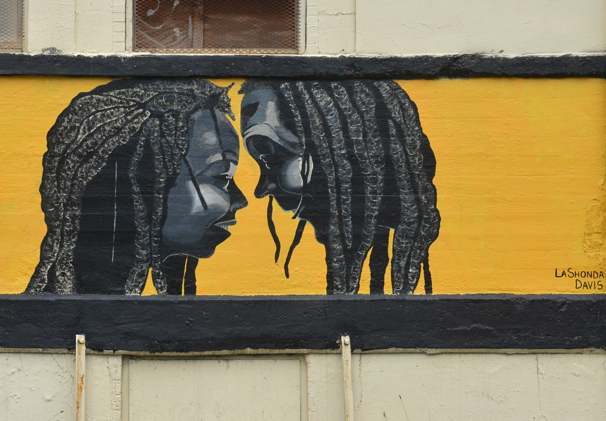 A mural by LanShonda Davis, yellow background, two faces in profile, both black tieh dreadlocks, one man, one woman, they are face to face and their noses are almost touching.