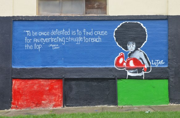"A mural on the side of a building. Blue background. A young man with an Afro hair style is wearing red boxing gloves. The words on the mural say "" To be once defeated is to find cause for an everlasting struggle to reach the top"" It is a quote attributed to Marcus Garvey. The mural is signed by Lujar."