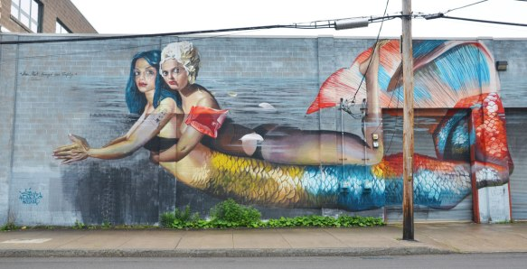 A large mural of a mermaid swimming in the water with another woman on her back - the other woman is wearing a white bathing cap and orange arm floaties.