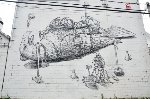 Wall Therapy mural in Rochester, on the side of a building, black line drawing of a very large eagle on its back, tied down as well as locked and chained. A soldier with a machine gun is guarding the eagle.