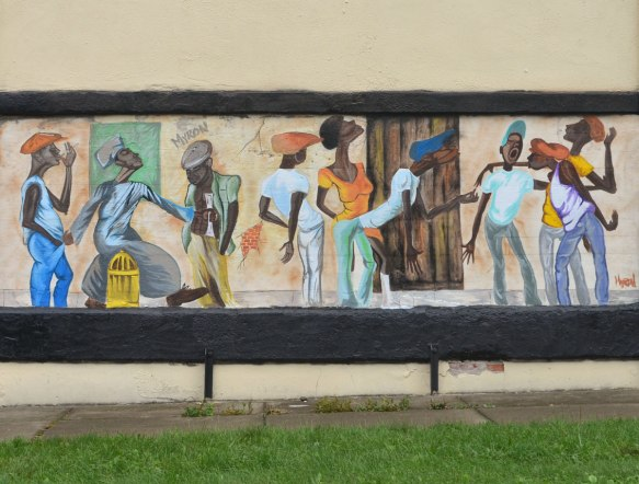 A mural by Myron Hall on the side of a wall of many people, mostly men, standing around talking, singing and generally being social.