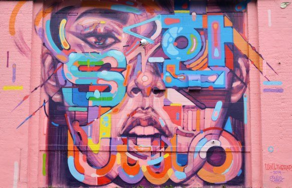 Mural of a large pink and purple face with letters in different colours painted on top of parts of it. One eye, nose and open mouth are visible.