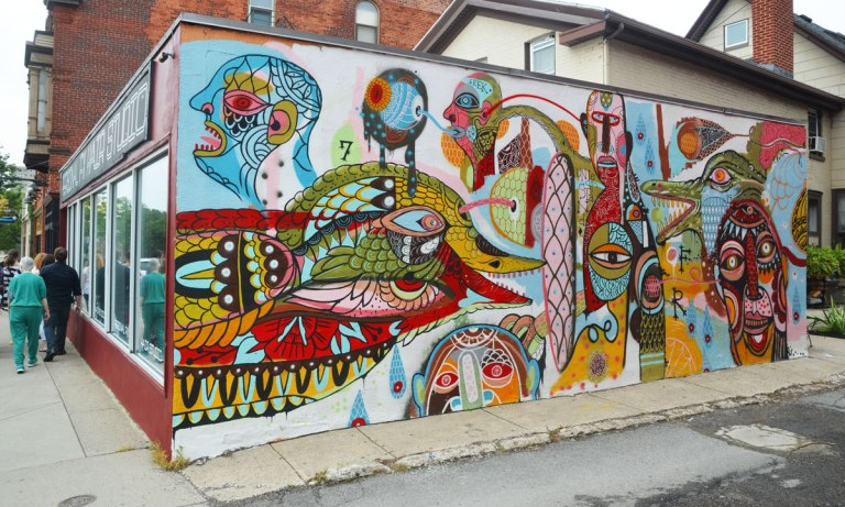 "colourful mural of abstract figues, faces, birds, and fish on the side of a building, There is one word written on mural and it is ""understand"""