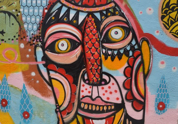 "detail of one of the faces in a colourful mural of abstract figues, faces, birds, and fish on the side of a building, There is one word written on mural and it is ""understand"""