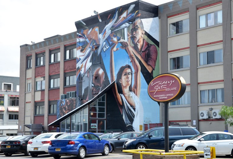 large mural of active people over the front entrance of a three storey building,